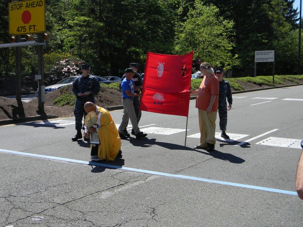 Larry Kerschner (in red shirt), Br. Gilberto Perez, and Bernie Meyer (in blue shirt) blocking traffic onto the Bangor Trident base during their nonviolent direct action.
